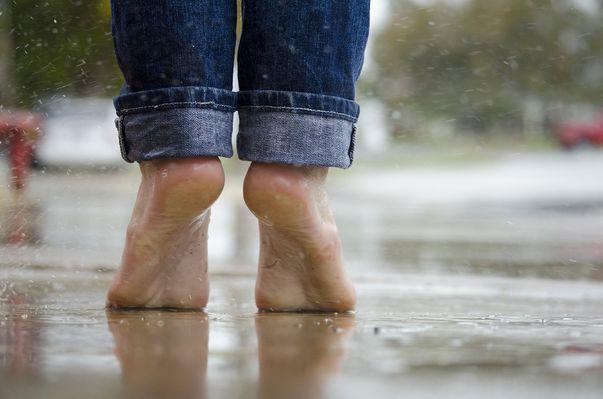 Negii plantari sunt produși de virusul HPV. Imagine cu femeie care merge în picioarele goale ceea ce poate conduce la contractarea virusului HPV la nivelul tălpii