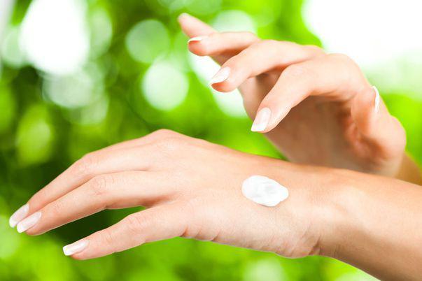 Crema cu camfor. Femeie care aplica crema pe mana (detaliu)