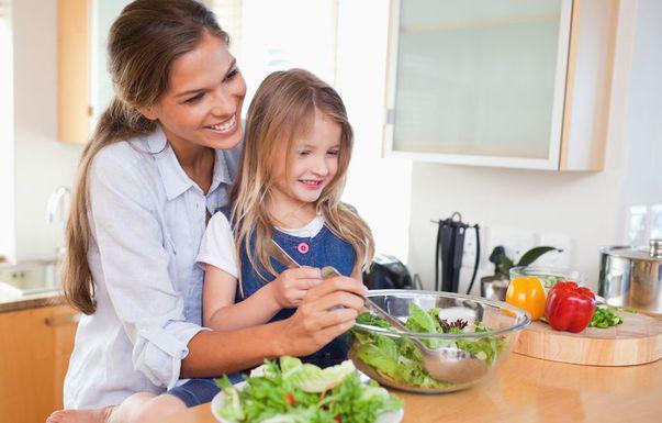 Cum îți înveți copilul să fie responsabil. Mamă și fiica prepară salată în bucătărie