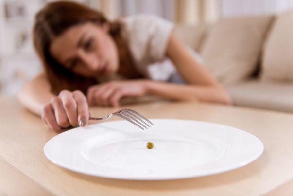 Cum recunoști un anorexic: mănâncă porții foarte mici. Fată epuizată mănâncă o boabă de mazăre cu furculița