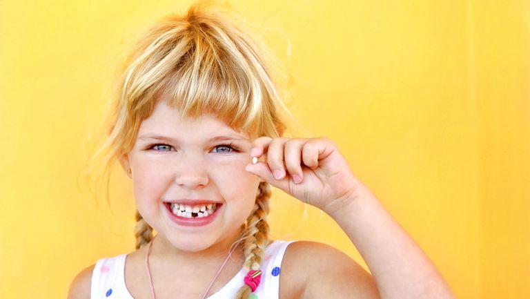 Cine este Zâna Măseluță si ce cadouri aduce - fetita cu un dinte in mana