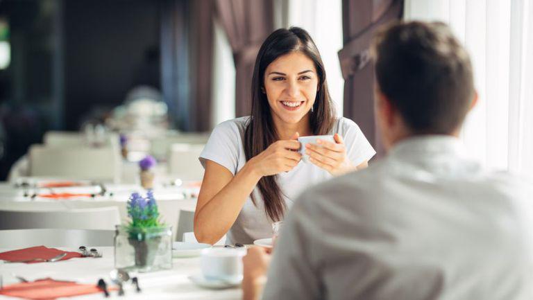 Tânără care îi zâmbește partenerului în timp ce se află la o cafea