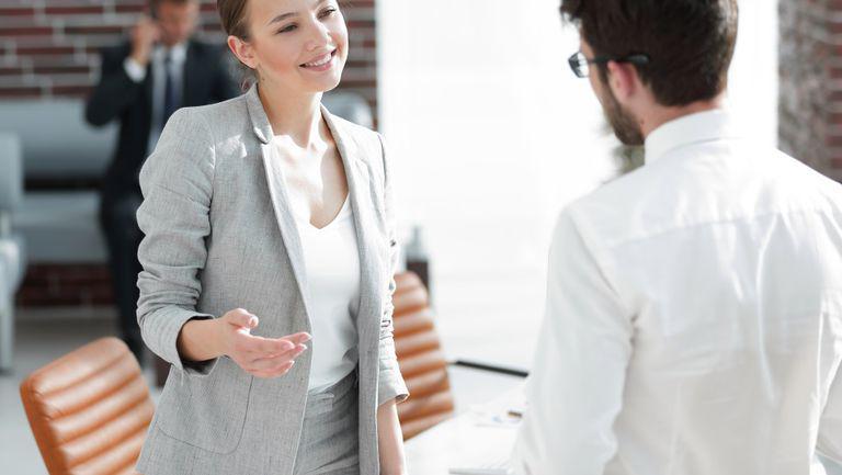 Gestul banal care la prima întânire îți poate distruge imaginea - o femeie imbracata office zambeste si ii explica ceva unui barbat