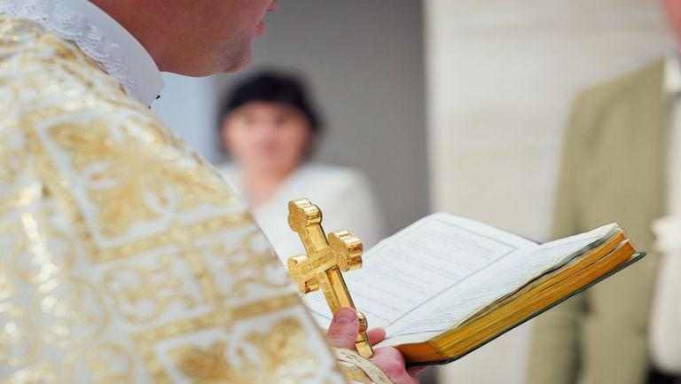Un preot tine in mână Biblia și o Cruce